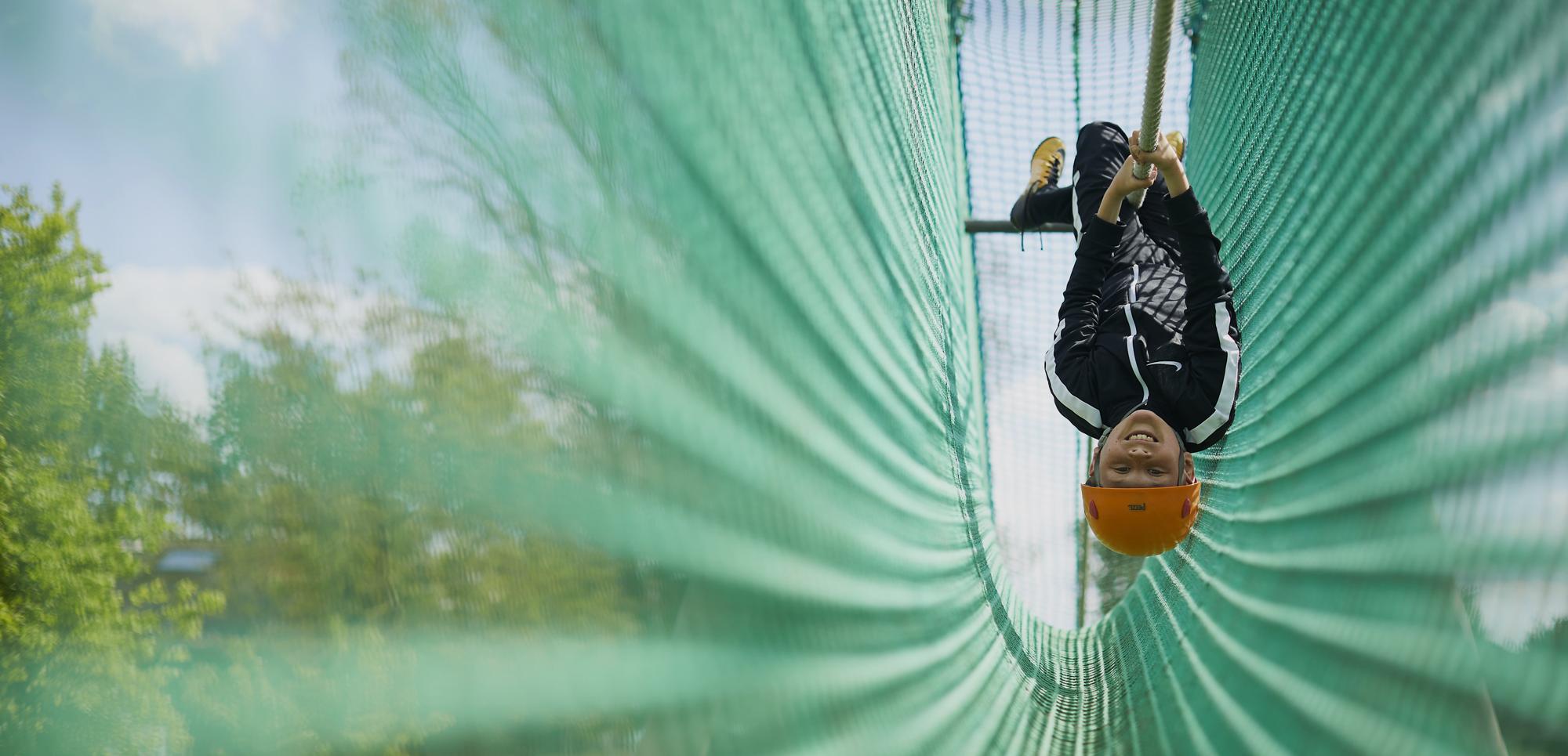 boy in orange helmet hanging upside down on a cargo net